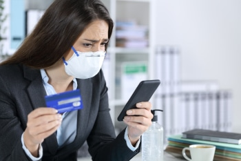 Worried executive woman pays with credit card on smart phone avoiding covid-19 sitting at the office