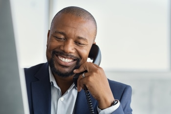Close up face of mature businessman working on computer and talking on phone. Mature african man talking on mobile phone at desk in office. Smiling manager working at desk with copy space.