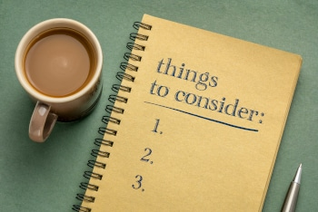 things to consider list - handwriting in a notebook with a cup of ocffee, business planning concept