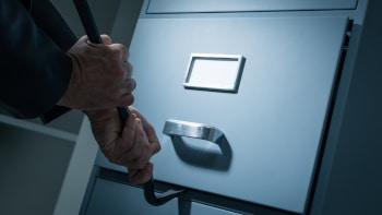 Burglar opening a drawer in the office at night using a crowbar he is stealing confidential data and information data theft and security concept