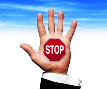 a photo image of a business man's hand with a stop sign ** Note: Slight graininess, best at smaller sizes
