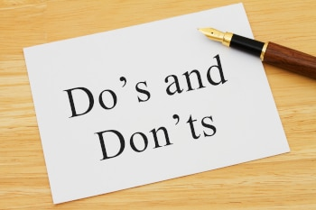 Learning to use proper grammar A white card on a desk with a pen with words Do's and Don'ts